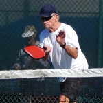 Man hits ball over net in Pickleball Tournament at Tampa Bay Senior Games 2013, Sun City Center, Florida [DAY ONE: Friday, October 25, 2013]
